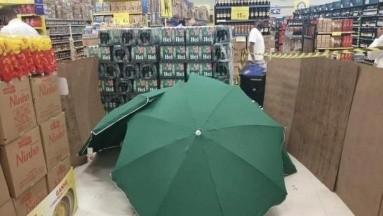 ¡Indignante! Muere trabajador de supermercado, lo cubren con paraguas y siguen trabajando